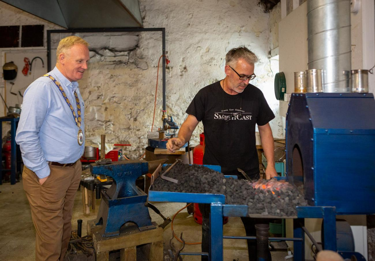 The Mayor watches sculptor Ned Jackson Smyth at work during a visit to his studio.